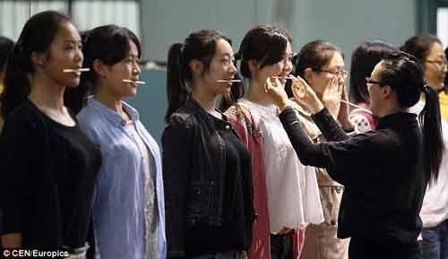 Thanh thiếu niên Trung Quốc cắn đũa trong miệng để tập mỉm cười