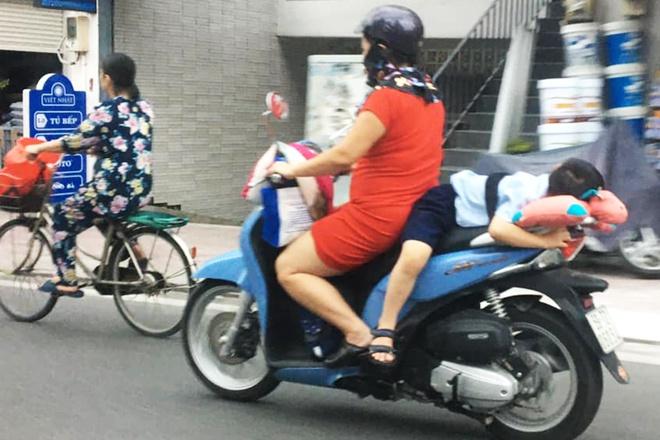 Thót tim cảnh người phụ nữ chạy xe, buộc con nằm dài trên yên  - ảnh 1