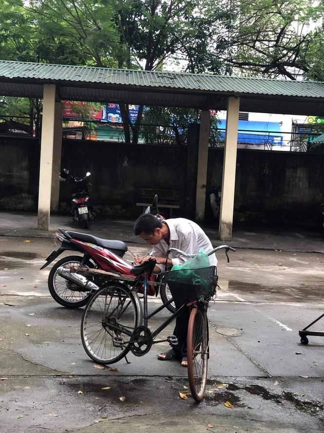 """Hình ảnh người cha đi xe đạp cũ, dùng điện thoại dán chằng chịt chụp điểm thi cho con gây """"sốt"""" mạng xã hội - ảnh 1"""