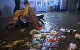 """Người Hà Nội dầm mưa, bì bõm rẽ """"biển nước"""" ngập rác để về nhà"""