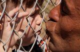 Tin thế giới - Cảm động hình ảnh ông bố hôn con qua hàng rào trại tị nạn sau một năm xa cách