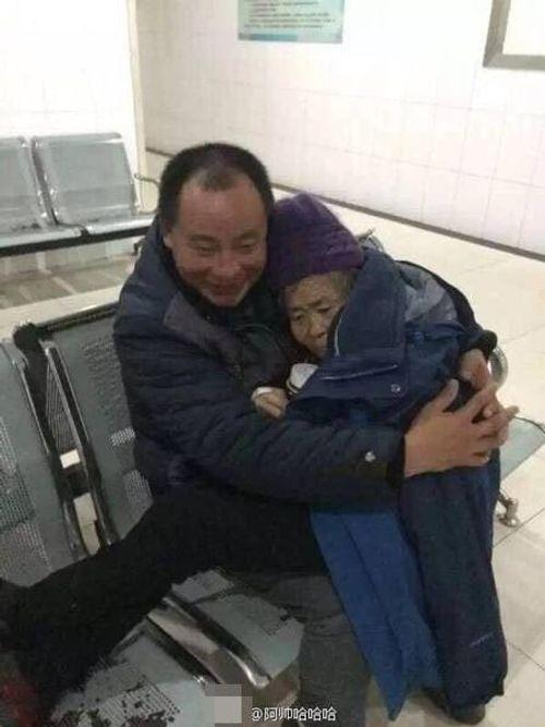 Cảm động hình ảnh con trai ôm mẹ già đợi khám bệnh - Ảnh 1