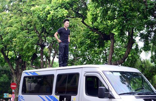 Ảo thuật gia 9X ngồi lơ lửng trên nóc ô tô đọc báo ở Hà Nội - Ảnh 1
