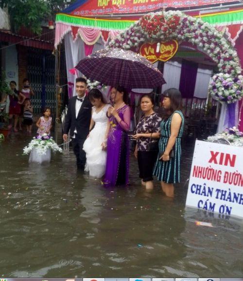 Cô dâu chú rể bì bõm lội nước tiếp khách giữa trời mưa dậy sóng mạng - Ảnh 1