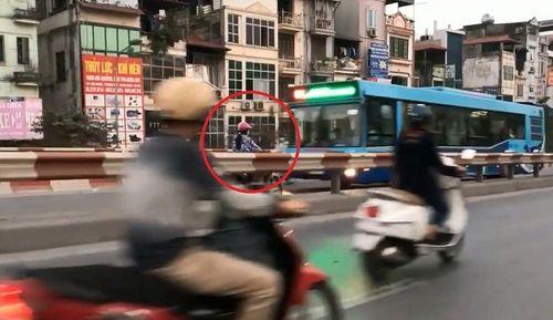 Thót tim người phụ nữ chạy xe máy ngược chiều trên cầu vượt, suýt đấu đầu xe buýt - Ảnh 1