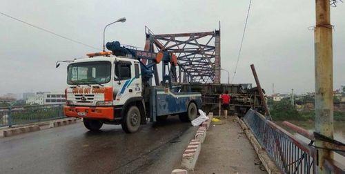 Ôtô tải nổ lốp và lật nghiêng trên cầu, 2 mẹ con thương vong - Ảnh 1