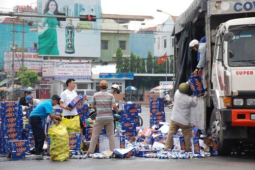 Người dân giúp tài xế thu gom hàng trăm thùng bia rơi trên đường - Ảnh 1