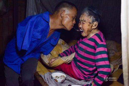 Video: Con trai tật nguyền dùng miệng bón thức ăn cho mẹ già 91 tuổi - Ảnh 1