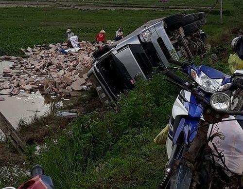 Hình ảnh đẹp: Xe container bị lật, người dân Phú Yên giúp tài xế đưa hàng trăm lon nước lên bờ - Ảnh 1