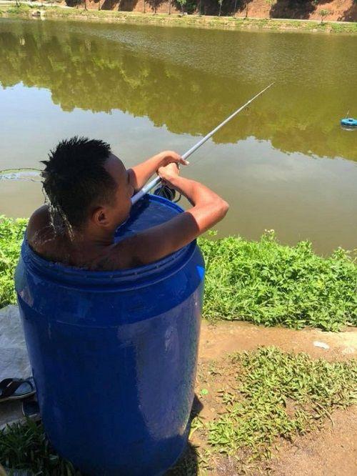 Thời tiết nắng nóng 40 độ, người đàn ông ngâm mình trong thùng phuy đầy nước để câu cá  - Ảnh 1