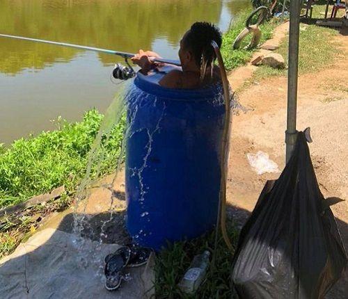 Thời tiết nắng nóng 40 độ, người đàn ông ngâm mình trong thùng phuy đầy nước để câu cá  - Ảnh 3