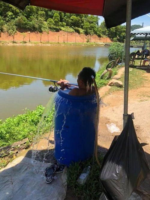 Thời tiết nắng nóng 40 độ, người đàn ông ngâm mình trong thùng phuy đầy nước để câu cá  - Ảnh 2