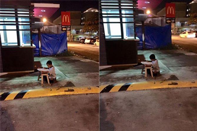 Xót xa em bé ngồi học ngoài đường nhờ ánh sáng từ quán ăn