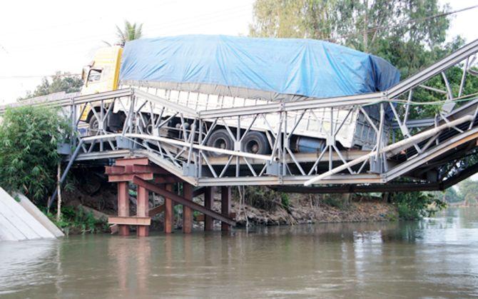 Xe chở 46 khối gỗ lơ lửng trên cầu sập - Ảnh 1