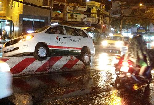Tránh xe máy, taxi leo lên trên dải phân cách trong mưa - Ảnh 1