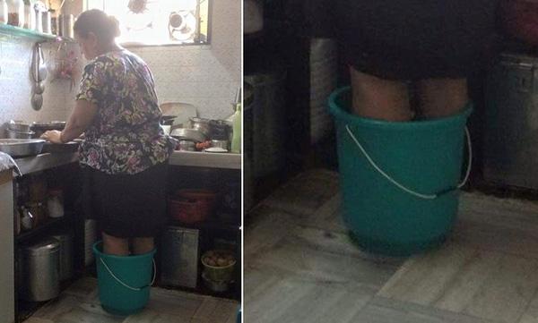Người mẹ đứng trong xô nước nóng để nấu bữa ăn sáng cho con - Ảnh 1
