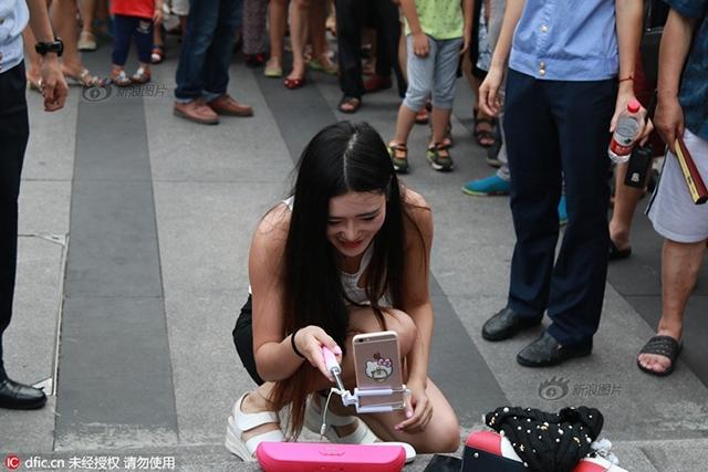 Cô gái trẻ mặc khêu gợi, uốn éo, livestream giữa phố đông người - Ảnh 3