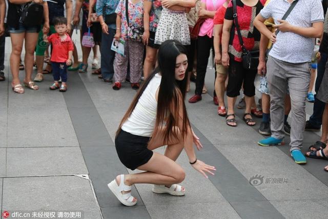 Cô gái trẻ mặc khêu gợi, uốn éo, livestream giữa phố đông người - Ảnh 4