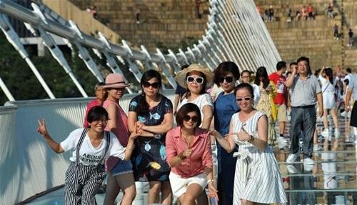 Hàng ngàn du khách nhồi nhét trên cầu đáy kính dài và cao nhất thế giới - Ảnh 13