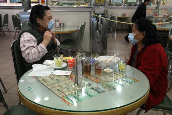 Để phòng dịch bệnh, nhà hàng ở Hồng Kông đặt tấm ngăn trên bàn ăn - Ảnh 1