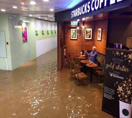 Người đàn ông thản nhiên ngồi đọc báo giữa quán café lụt lội - Ảnh 1