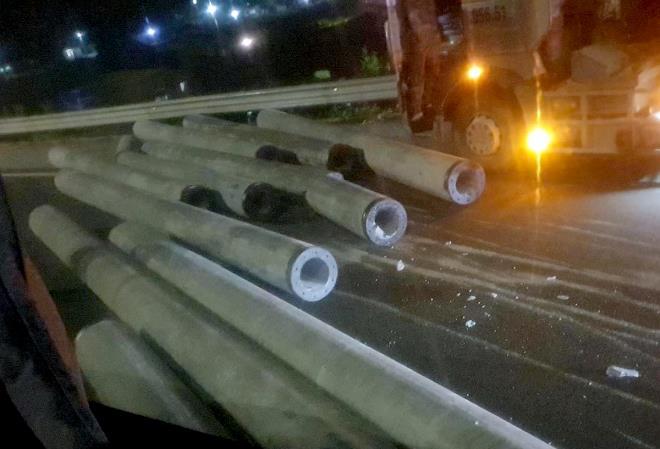 Cột điện rơi từ container xuống cao tốc, văng trúng xe khách - Ảnh 1