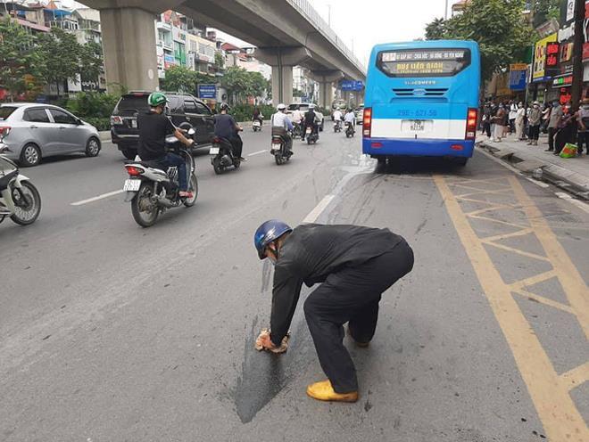 """""""Bác tài"""" hì hục lau vết dầu loang trên phố Hà Nội gây sốt cộng đồng mạng - Ảnh 1"""