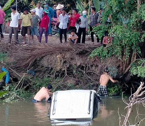 Ô tô tụt dốc rơi xuống kênh nước, 2 cha con bung cửa thoát thân - Ảnh 1