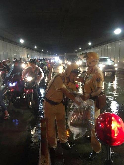 Hai chiến sĩ CSGT phát áo mưa miễn phí cho người dân trong hầm Thủ Thiêm vào đêm Trung thu - Ảnh 1