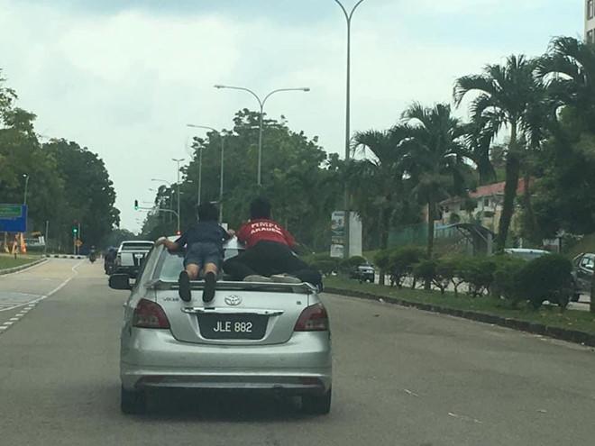 """""""Lạnh sống lưng"""" khi chứng kiến 2 bé trai nằm vắt vẻo trên nắp cốp xe ôtô đang chạy - Ảnh 1"""