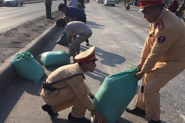 Người dân và CSGT cùng nhau giúp tài xế thu gom 10 tấn ngô rơi kín mặt cầu - Ảnh 2