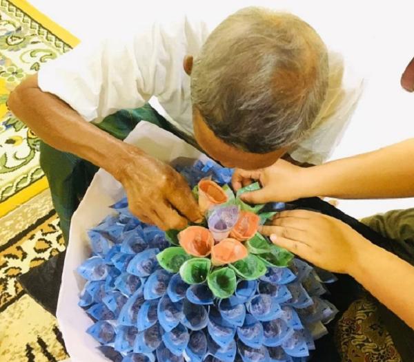Câu chuyện xúc động phía sau hình ảnh cha già cặm cụi giúp con gái chuẩn bị bó hoa tiền - Ảnh 1