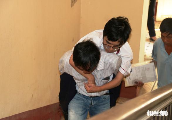 Xúc động hình ảnh bố đeo chân giả cõng con trai vào tận phòng thi - Ảnh 1