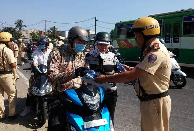 CSGT TP.HCM phát nước, khăn lạnh miễn phí cho người dân trên đường về quê ăn Tết - Ảnh 1