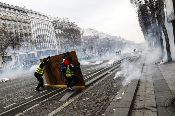 Cận cảnh cuộc đụng độ giữa hàng ngàn người biểu tình với cảnh sát Paris - Ảnh 10
