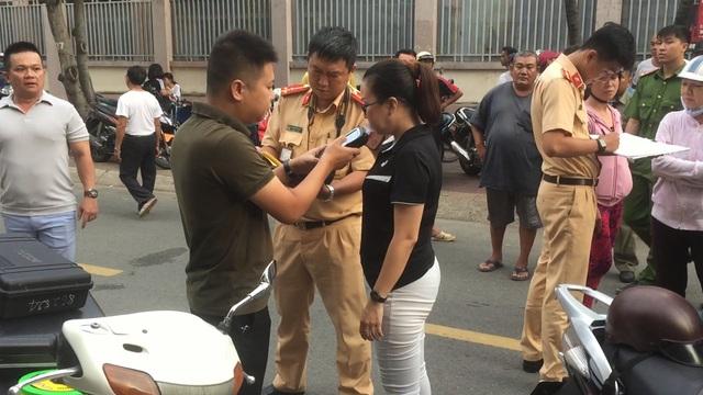 Lực lượng công an tiến hành đo nồng độ c ồn đối với người phụ nữ lái ô tô gây tai n ạn. Ảnh: Dân Trí