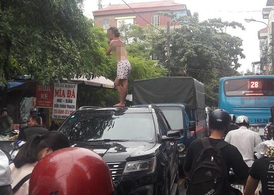 Cô gái trèo lên nóc ô tô nhảy múa khiến cả tuyến phố ở Hà Nội ùn tắc - Ảnh 1