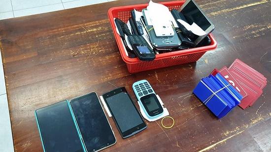 Tang vật thu giữ gồm nhiều điện thoại và thẻ nhựa để con b ạc đặt cược. Ảnh: PLO