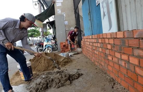 Triều cường dâng cao, người dân TP.HCM hối hả xây tường, đắp bao ngăn nước - Ảnh 7