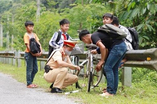 Cảnh sát giao thông sửa xe bên đường cho học sinh - Ảnh 1