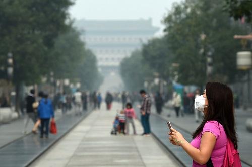 Người dân Bắc Kinh vẫn đeo khẩu trang dù quy định bắt buộc đã được gỡ bỏ - Ảnh 1