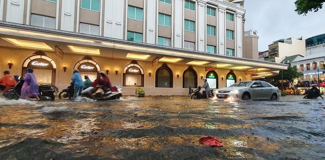 Mưa lớn gây ngập cục bộ nhiều tuyến phố Hà Nội, người dân loay hoay quét nước ra khỏi nhà - Ảnh 1