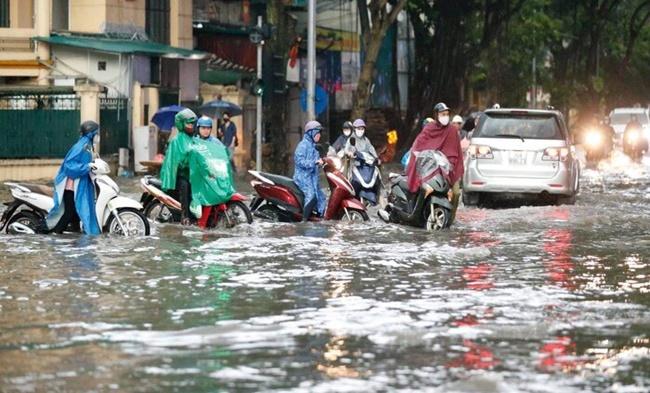 Mưa lớn gây ngập cục bộ nhiều tuyến phố Hà Nội, người dân loay hoay quét nước ra khỏi nhà - Ảnh 3