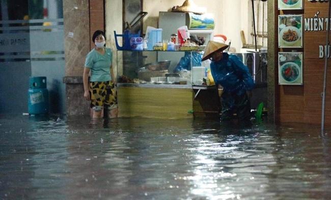 Mưa lớn gây ngập cục bộ nhiều tuyến phố Hà Nội, người dân loay hoay quét nước ra khỏi nhà - Ảnh 6