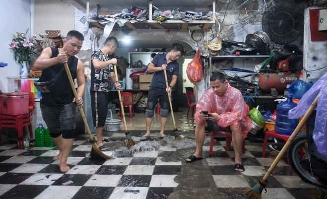 Mưa lớn gây ngập cục bộ nhiều tuyến phố Hà Nội, người dân loay hoay quét nước ra khỏi nhà - Ảnh 8