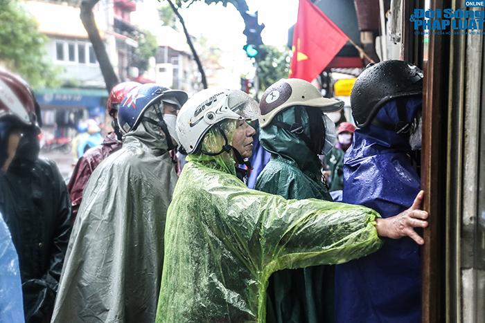 Người Hà Nội đội mưa, xếp hàng dài như thời bao cấp để mua bánh chưng nổi tiếng - Ảnh 10