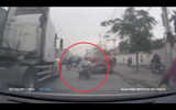 Xe máy chở cồng kềnh suýt chết khi ngã vào container