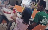 Bức ảnh người cha nghèo nhìn 2 con gái say sưa ăn gà rán gây sốt dân mạng