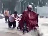 Xúc động hình ảnh 2 nam sinh dầm mình dưới mưa đẩy xe giúp người dân giữa dòng nước xiết
