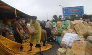 Container chở hoa quả lật nghiêng, dân đội mưa khiêng hàng giúp tài xế